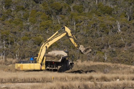 replanting: a 40 ton digger uses a special bucket to load native vegetation for replanting after mining at an open cast coal mine in New Zealand