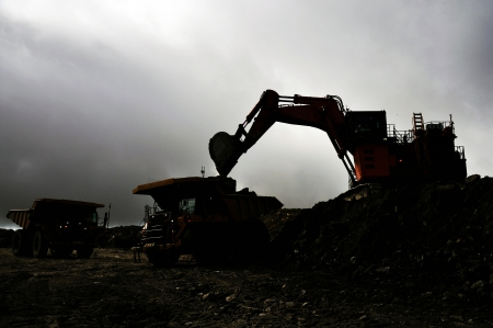 silhouette of a 190 ton digger loading a 130 ton tiptruck with rock overburden at an open cast coal mine