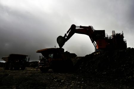 silueta de una excavadora 190 toneladas de cargar un tiptruck 130 toneladas con sobrecargar roca en una mina de carbón a cielo abierto Foto de archivo