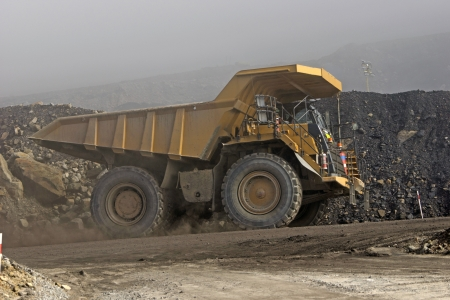 a 130 ton tiptruck emerges from the mist at an open cast coal mine, Westland, New Zealand photo