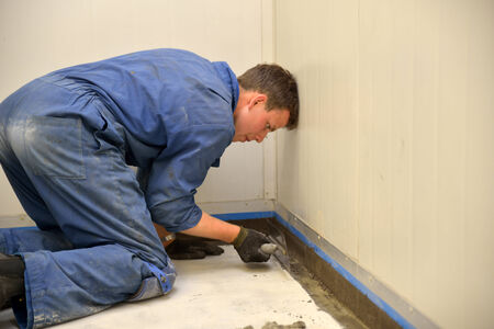 epoxy: tradesman applying epoxy product to coving around the floor of an industrial building