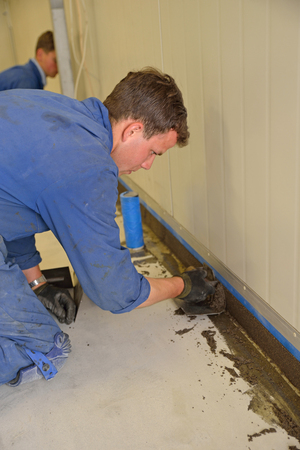 tradesman applying epoxy product to coving around the floor of an industrial building photo