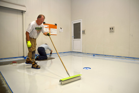 bedrijfshal: handelaar toepassen epoxy product op de vloer van een industrieel gebouw