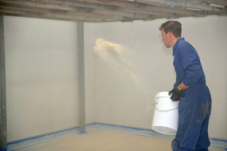 epoxy: tradesman spreading sand over epoxy product on floor of an industrial building Stock Photo