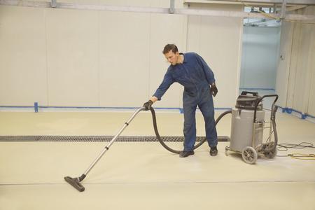 handelaar stofzuigers verdieping van een industrieel gebouw in voorbereiding voor het schilderen
