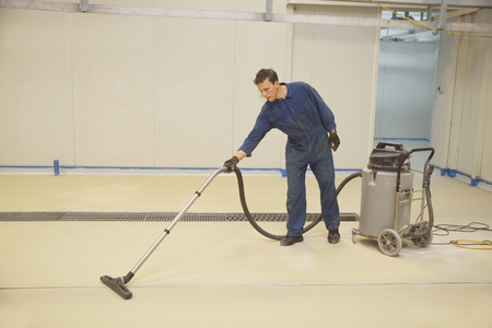tradesman vacuums floor of an industrial building in preparation for painting