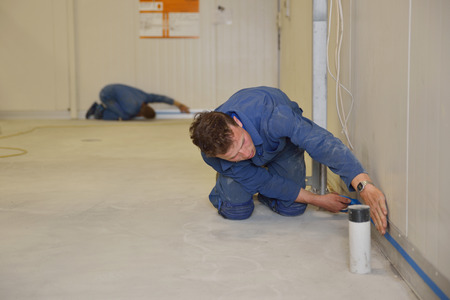 epoxy: tradesman masks off the height of the coving before applying epoxy product to the floor of an industrial building