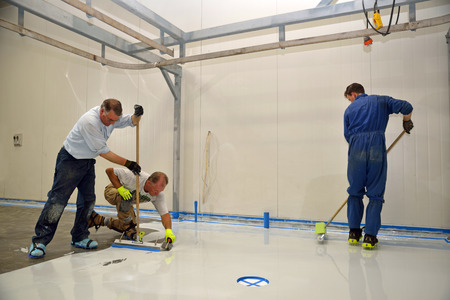 tradesman applying epoxy product to floor of an industrial building Stok Fotoğraf - 25687404