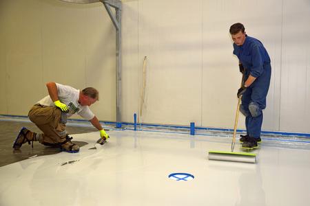 handelaar toepassen epoxy product op de vloer van een industrieel gebouw