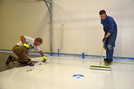 epoxy: tradesman applying epoxy product to floor of an industrial building Stock Photo