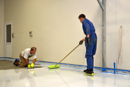 tradesman applying epoxy product to floor of an industrial building Standard-Bild