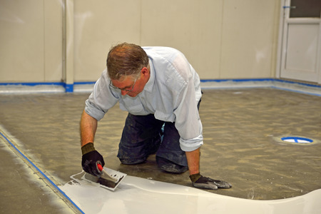 tradesman applying epoxy product to floor of an industrial building Stok Fotoğraf