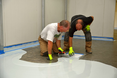 tradesman applying epoxy product to floor of an industrial building Stok Fotoğraf - 25687409