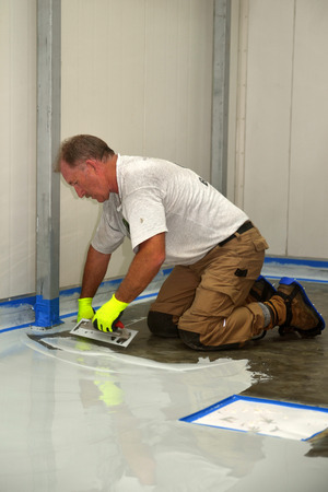 tradesman applying epoxy product to floor of an industrial building Stock Photo