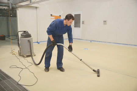tradesman vacuums floor of an industrial building in preparation for painting Stock Photo - 25687272