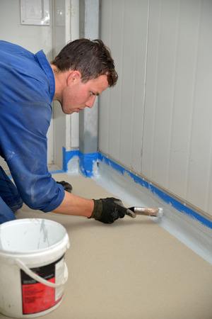 tradesman painting edge of floor line before epoxy product is used in an industrial building