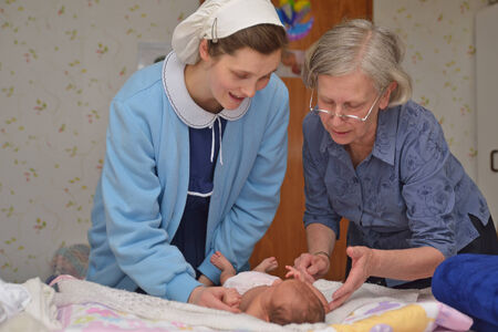 midwifery: A senior midwife checks a newborn baby with her mother