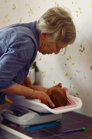 midwifery: A senior midwife weighs a young baby as part of her post-natal check Stock Photo
