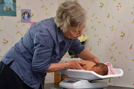 A senior midwife weighs a young baby as part of its post-natal check