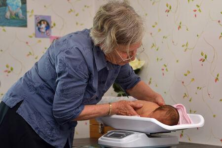 Ein leitender Hebamme wiegt ein junges Baby als Teil seiner postnatalen Check Standard-Bild - 25686910