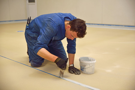 epoxy: tradesman painting edge of floor line before epoxy product is used in an industrial building