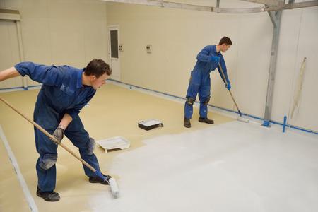 handelaars rollen laatste laag epoxy product op de vloer van een industrieel gebouw