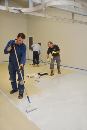 エポキシ樹脂製品の最終的なコートを工業用建物の床に転がり商人
