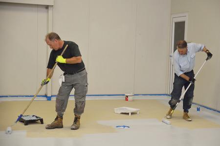 handelaars rollend laatste laag epoxy product op de vloer van een industrieel gebouw