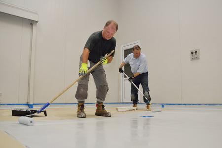 suelos: comerciantes y laminadores capa final de epoxi producto en el piso de un edificio industrial