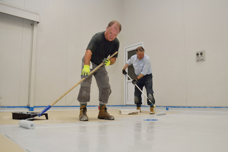 painter: tradesmen rolling final coat of epoxy product on the floor of an industrial building