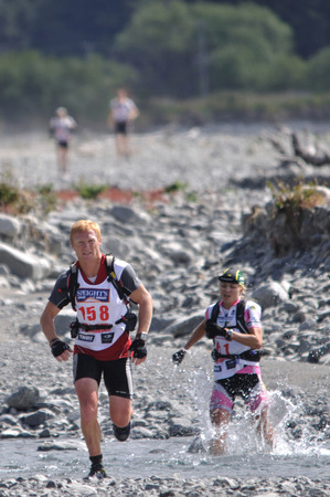 something athletic: SOUTH ISLAND, NEW ZEALAND, FEBRUARY 12, 2011: John Mudgway just keeps ahead of Elina Ussher, the second-place winner in the womens section, in the mountain leg of the 2011 Coast to Coast triathlon, West Coast, South Island, New Zealand