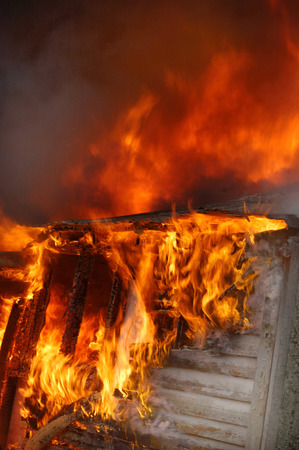 flames and smoke rise from burning farm building