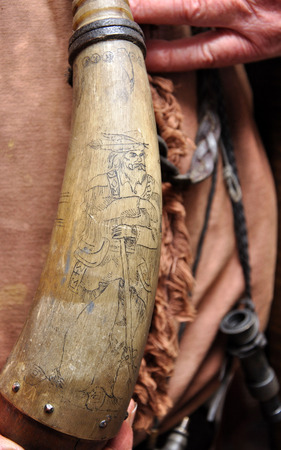 flintlock: decoration of a buckskinned pioneer on a powder horn used for a blackpowder flintlock rifle Stock Photo