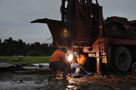 exploratory: MOANA, NEW ZEALAND, MARCH 9, 2010: Drilling crewmen weld another pre-collar pipe in place for an exploratory well for coal seam gas on the West Coast of New Zealand