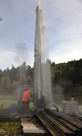 'rig out': MOANA, NEW ZEALAND, MARCH 18, 2010: Drilling crewmen control a small blowout at the mouth of a well for coal seam  gas near Moana, New Zealand.