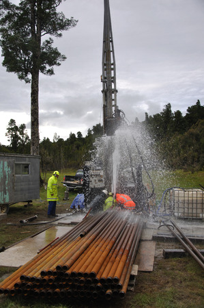 blowout: MOANA, NEW ZEALAND, MARCH 18, 2010: Drilling crewmen control a small blowout at the mouth of a well for coal seam  gas near Moana, New Zealand.