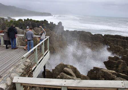orificio nasal: PUNAKAIKI, NUEVA ZELANDA, 05 de mayo 2010: Los turistas fotograf�an mientras que el espir�culo principal es en la acci�n en las rocas de la crepe, Punakaiki, costa oeste, Isla Sur, Nueva Zelanda Editorial