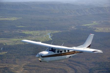 Cessna 210 경량 항공기가 뉴질랜드 서부의 수풀과 농장을 날기