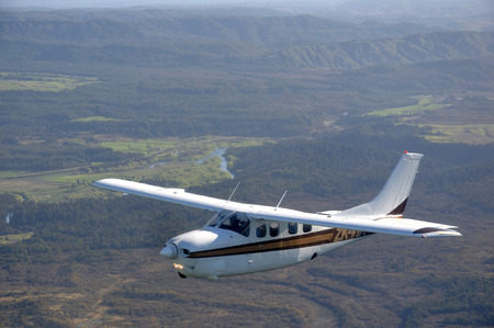 Cessna 210 light aircraft flying over bush and farms in Westland, New Zealand