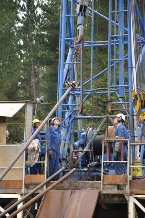 Drilling crewman prepare to lift a pipe into position on a rig drilling for crude oil near Moana, New Zealand. photo
