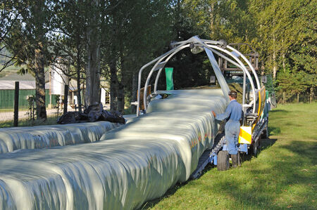 landuse: Continuous wrapper at work on square bales of hay, West Coast, New Zealand Stock Photo