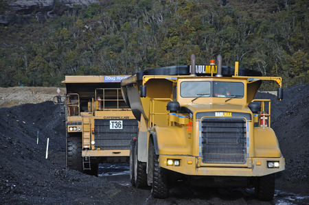 WESTPORT, NEW ZEALAND, JULY 20, 2009: Huge trucks move high grade coal from a stockpile at the Stockton Coal Mine near Westport, New Zealand