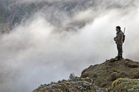 Hunter scoping for Himalayan tahr in the Southern Alps of New Zealand Reklamní fotografie