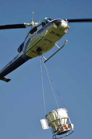 GREYMOUTH, NEW ZEALAND, CIRCA 2009: Iroquois helicopter takes off with a load of 1080 pellets in a monsoon bucket. The 1080 pellets are a controversial method of controlling possums in New Zealands native bush.