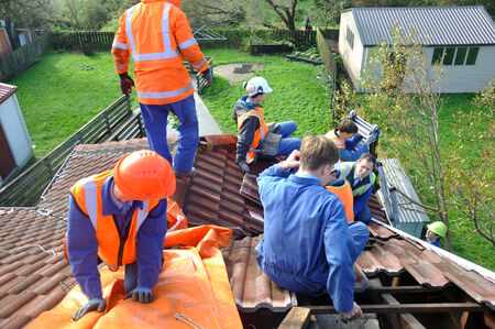 tarpaulin: GREYMOUTH, NEW ZEALAND, APRIL 17, 2014: Volunteer workers place a tarpaulin on a house de-roofed in Cobden by Cyclone Ita, Greymouth, New Zealand, April 17, 2014 Editorial