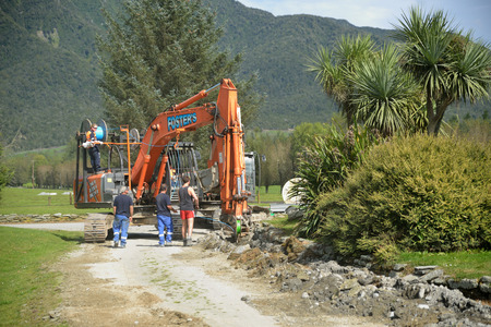 plough machine: GREYMOUTH, NEW ZEALAND, APRIL 1, 2014: Workers lay a fibre optic cable as part of a government scheme to bring high-speed internet connections to rural Westland, New Zealand