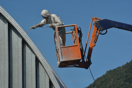 labouring: Tradesman spray painting the roof of an industrial building
