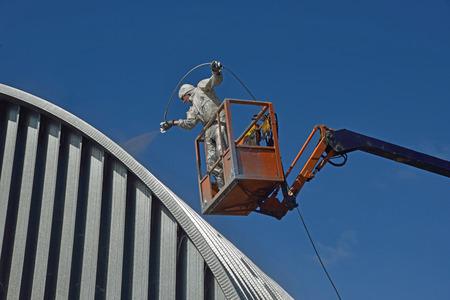 Tradesman het spuiten van het dak van een industrieel gebouw