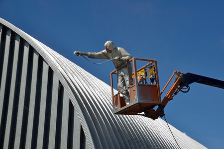 Tradesman spray painting the roof of an industrial building Stok Fotoğraf - 27931154