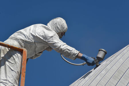 compressed air: Tradesman spray painting the roof of an industrial building